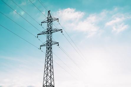 Strommast Überland vor blauem Himmel mit Wolken
