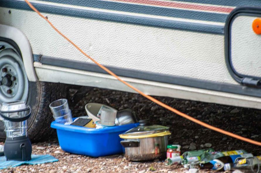 Spülschüssel mit schmutzigem Geschirr und leeren Flaschen unter einem Wohnwagen