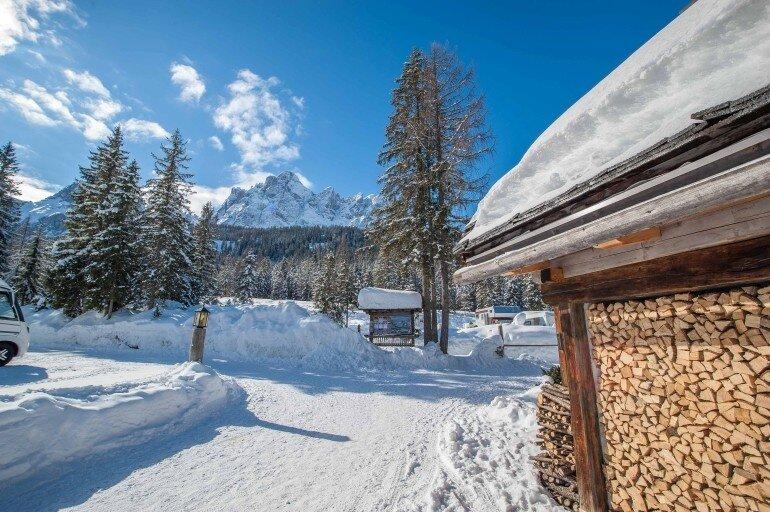 Caravan Park Sexten Camping Stellplätze im Schnee mit Bergen und blauem Himmel