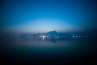 Blick auf den Gardasee bei Abendstimmung mit beleuchteter Stadt auf der gegenüberliegenden See Seite