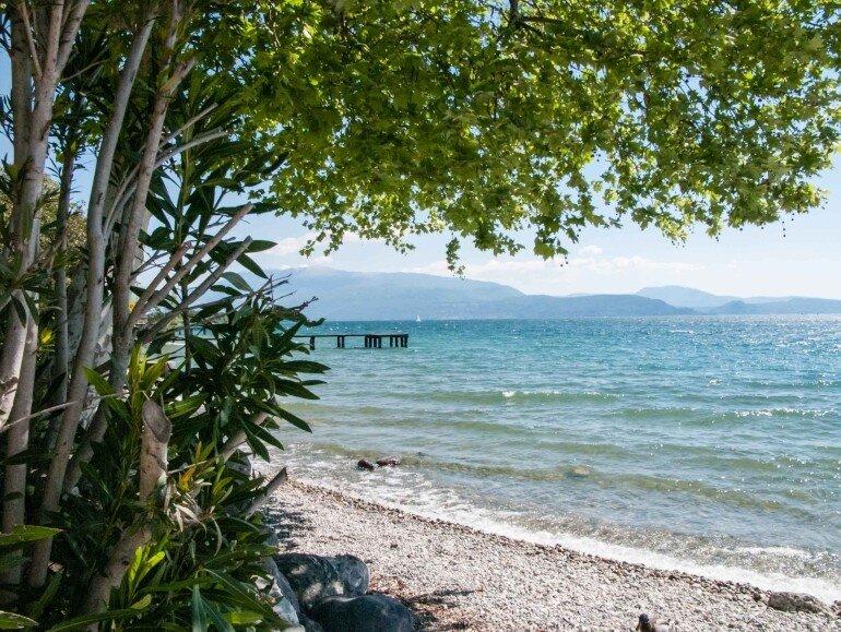 Blick vom Wohnwagen Stellplatz auf dem Camping Europa Silvella auf den Gardasee