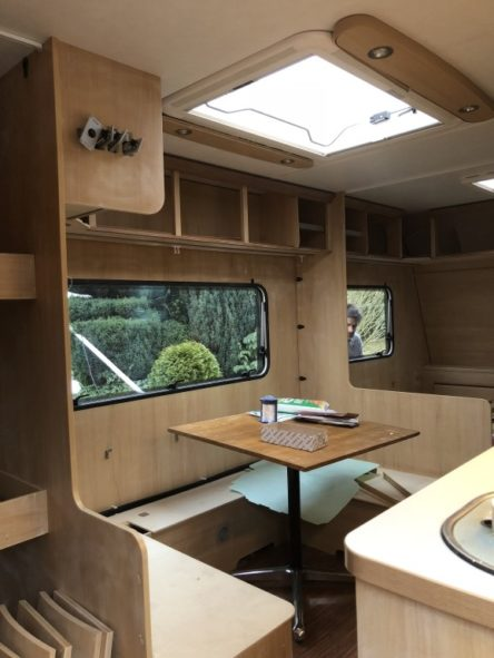 Essbereich im Wohnwagen mit angeschliffenem Holz und abgebauten Hängeschränken