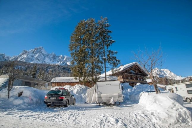 Winter Stellplatz mit Wohnwagen, Winter Vorzelt und BMW mit Blick auf die Berge