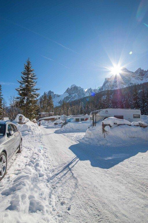 Durchfahrtsstraße auf dem Campingplatz schneebedeckt mit Sonne und Bergmassiv