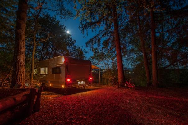 Wohnwagen mit Positionslichtern auf einem Stellplatz im Wald bei Nacht