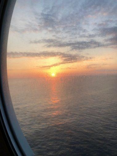 Blick aus dem Bullauge einer Außenkabine auf dne Sonnenaufgang am Horizont