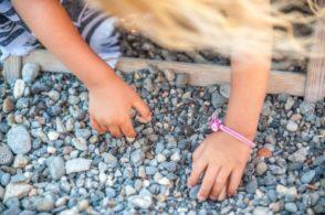 Kind beim Spielen mit Steinen am Strand