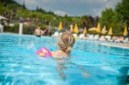 Kind mit Schwimmflügeln im Pool