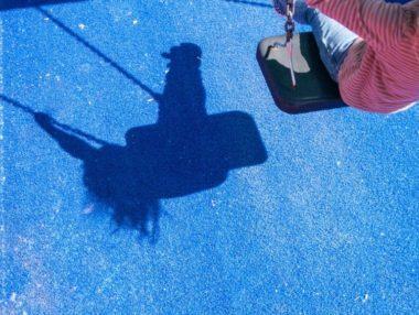 Schatten eines Kindes auf einer Schaukel auf einem Spielplatz