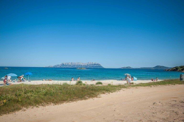 Strand mit Menschen und türkis Wasser mit Felsen im Meer auf Sardinien