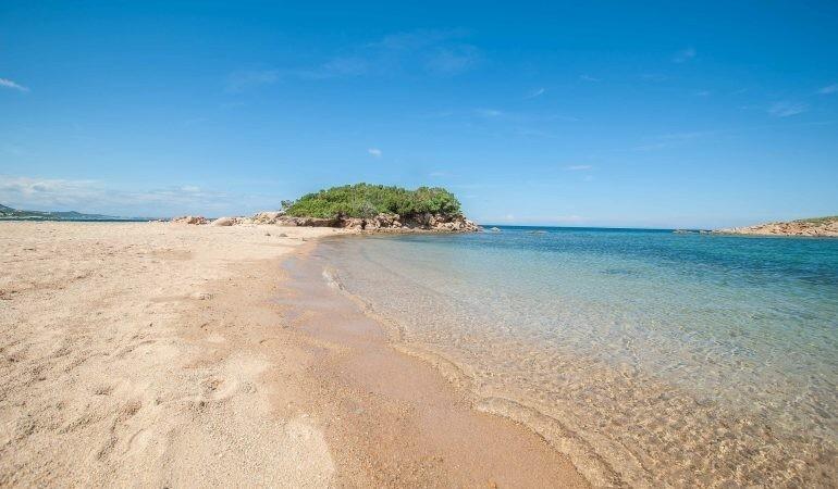 Strand mit glasklarem Wasser und Insel auf Sardinien