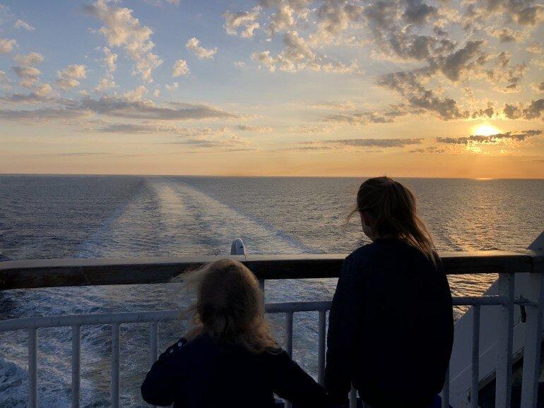 Kinder an der Reling der Mittelmeer Fähre blicken in den Sonnenuntergang