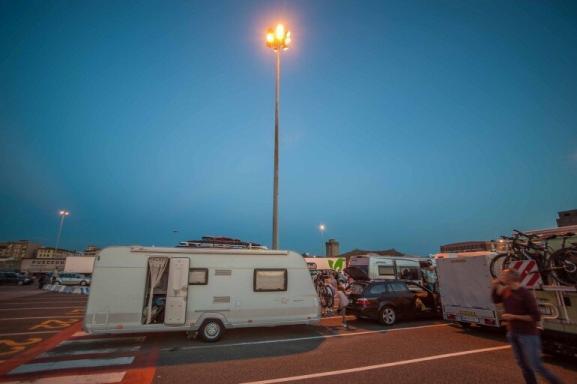 Wartezone für die Verschiffung im Hafen von Livorno mit dem Wohnwagen Gespann bei Dämmerung