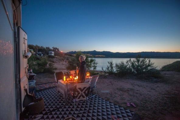 vord dem Wohnwagen Tisch mit vielen Kerzen und Blick auf das Meer mit Sonnenuntergang