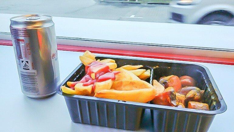 Currywurst Pommes mit Cola im Baumarkt Imbis