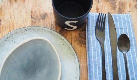 Gedeck auf dem Tisch beim Camping mit Besteck auf einem selbstgenähten Geschirrhandtuch