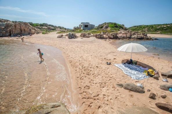 Strand auf La Maddalena gegenüber dem Campingplatz mit Schirm, Handtüchern und verfallenem Haus