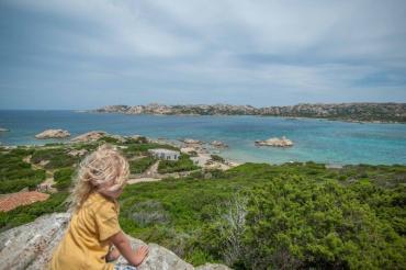 Kind auf einem Felsen mit Blick über eine Bucht auf La Maddalena