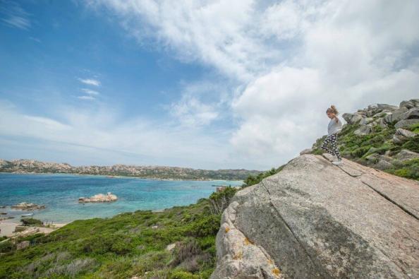 Kind auf einem Felsvorsprung mit Blick in eine Bucht auf La Maddalena