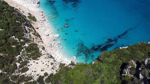 Luftaufnahme von einer Bucht mit felsigem Strand und Meer auf La Maddalena