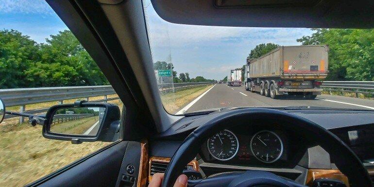 Blick vom Fahrersitz auf die Autobahn mit dem Wohnwagen Gespann beim Überholen von LKWs
