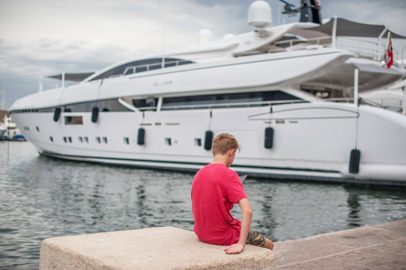 Junge vor riesiger Jacht im Hafen von Saint Tropez