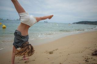 Plage de Pampelone - Kind schlägt ein Rad am StrandFelsenküste, türkises Wasser und Palmen