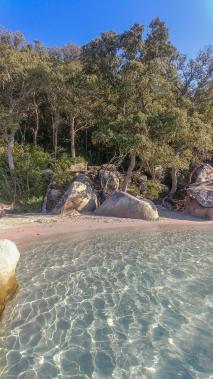 Steine und Strand mit blauem Wasser am Strand von Santa Giulia auf Korsika