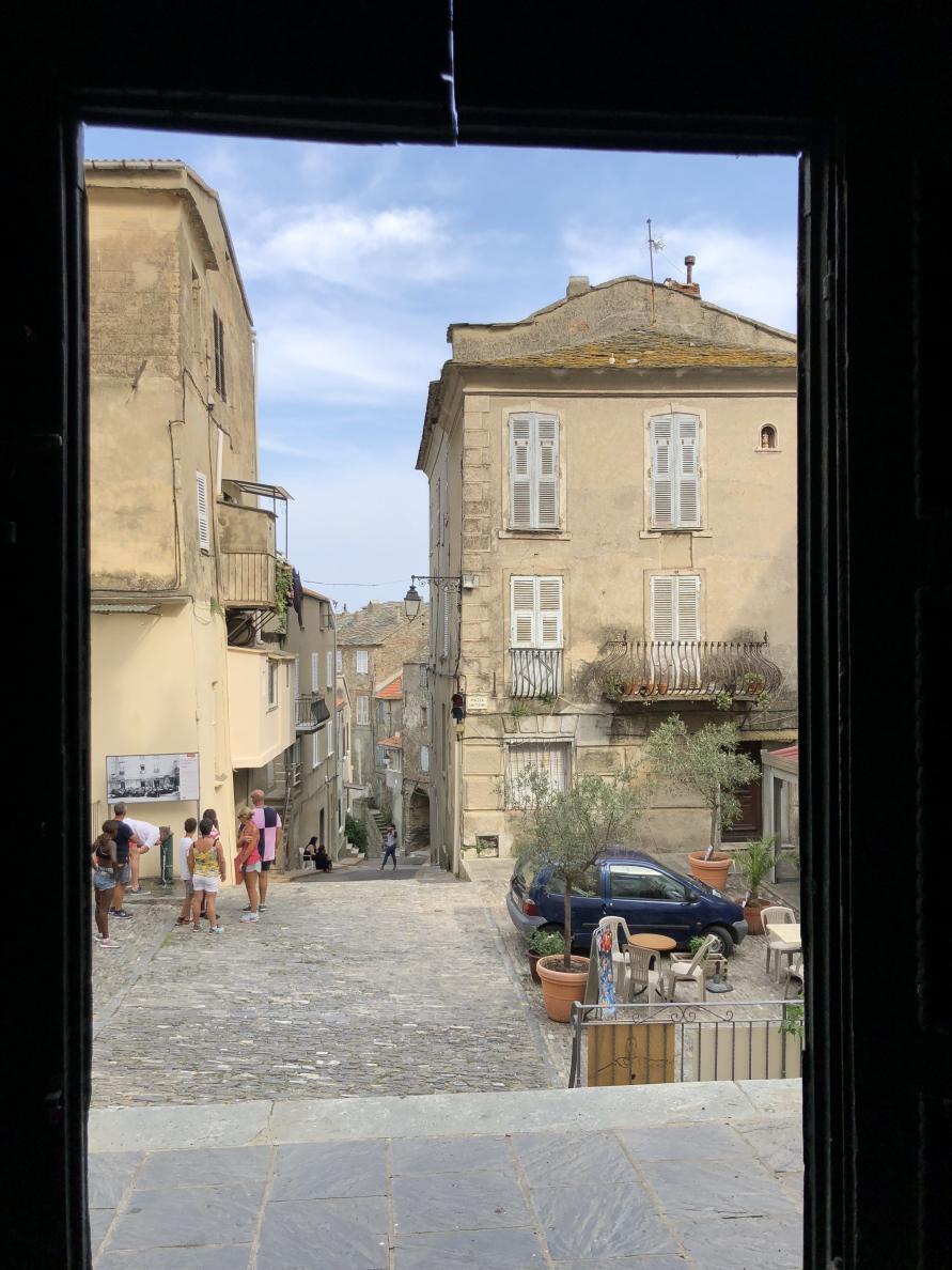 Blick aus einer Tür auf eine alte Gasse in einer Stadt auf Korsika
