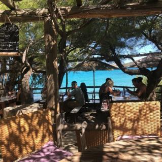 Restauraunt mit Blick auf das Meer unter Tannen auf Korsika