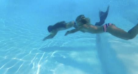 Kinder mit Merjungfrau Flossen unter Wasser beim Tauchen im Pool Le Campoloro