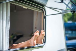 Kinder Füße hängen aus dem Wohnwagen Fenster im Sommerurlaub