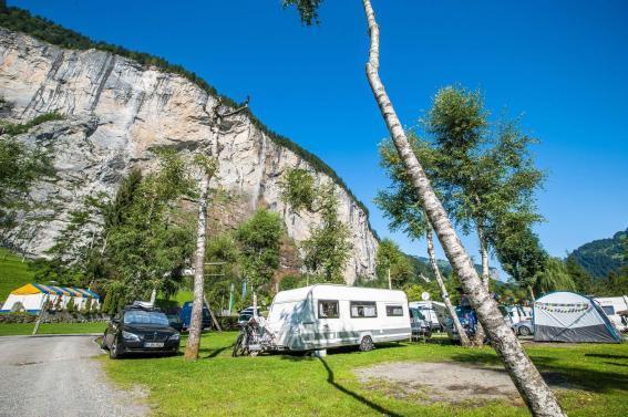 Campingplatz Jungfrau Holiday Park Schweiz Wohnwagen auf dem Stellplatz mit Wasserfällen im Sommer