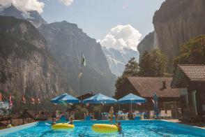 Schwimmbad in Lauterbrunnen mit zwei gelben großen Schwimmreifen und Blick ins Talende