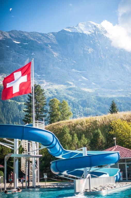 Schwimmbad in Grindelwald mit Rutsche, schweiter Fahne und der Eiger Nordwand im Hintergrund