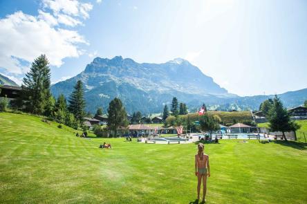 Schwimmbad in Grindelwald und Blick über die Liegewiese auf die Eiger Nordwand im Hintergrundmit Grindelwald im Hintergrund
