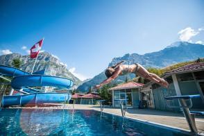 Freibad Hellbach in Grindelwald mit Bergen im Hintergrund und Kind springt Köpper vom Einer