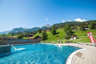 Freibad in Grindelwald mit Wieen und Almhütten im Hintergrund