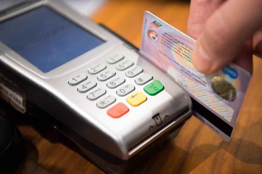 Kreditkarte die durch einenBezahl Terminal gezogen wird