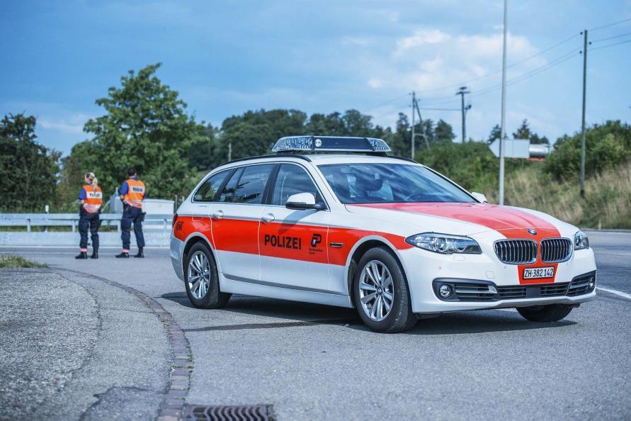 Schweizer Polizei mit PKW und zwei Polizisten bei einer Verkehrskontrolle