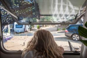 Blick aus dem Wohnwagen Fenster mit Kind, dass auf die gegenüberliegenden Stellplätze guckt