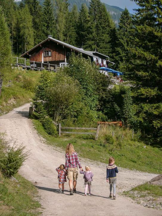 Berghütte im Sonnenschein mit einer Familie, die darauf zuläuftg Last Minute Camping Empfehlung Herbsturlaub