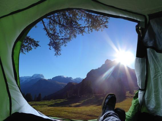 Blick aus einem Zelt auf ein Bergpanorama mit Wieden, Bäumen und Gipfeln