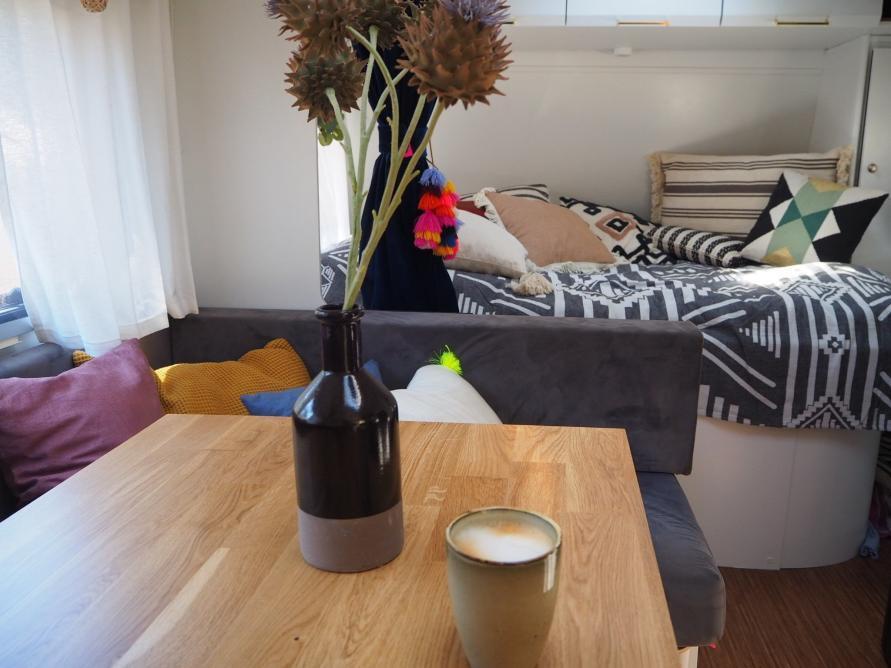 Fertiger Tisch mit Eichenparkett im Wohnwagen ein Cafe auf dem Tisch dahinter das Bett mit Kissen