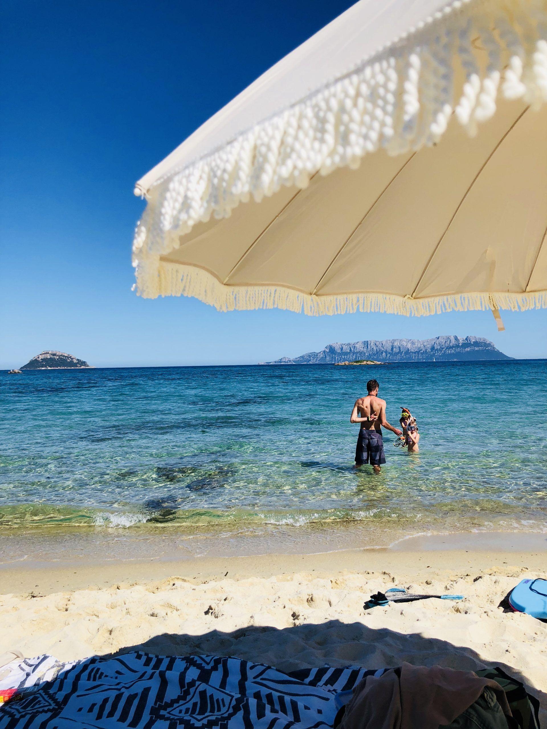 Meer und creme farbener Sonnenschirm am Strand im Hintergrund ein Berg