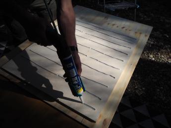 Alte Holzplatte wird mit Montagekleber vorbereitet damit Parkett auf die Tischplatte für den Wohnwagen geklebt werden kann