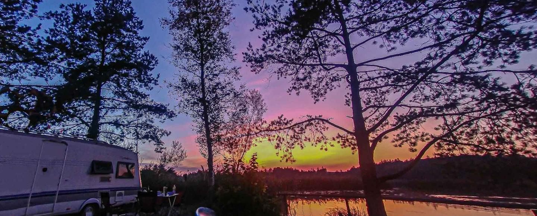 Sonnenuntergang am See mit Wohnwagen und Schatten der Tannen