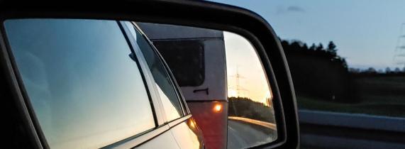 im Rückspiegel der Wohnwagen auf der Autobahn in der Abendsonne