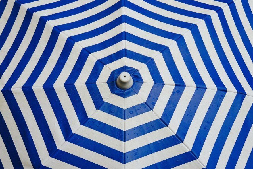 Muster eines blau gestreiften Retro Sonnenschirms