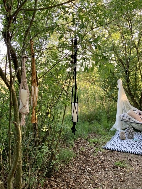 Garten mit hängenden Kerzen im Baum mit einem Tagesbett und Outdoorteppich